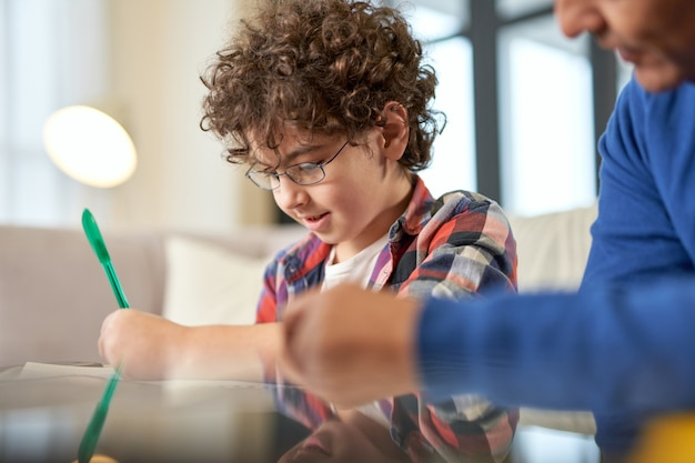 好奇心旺盛なラテン系の男子生徒が、家の机に座って、お父さんと一緒に宿題をしながら、集中して紙に書いています。遠隔学習、家族、父性の概念