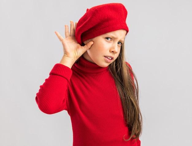 빨간 베레모를 쓰고 앞을 바라보는 호기심 많은 금발 소녀는 복사 공간이 있는 흰 벽에 격리된 당신의 몸짓을 들을 수 없습니다