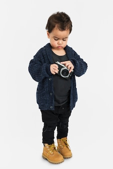 Curious little boy holding camera concept