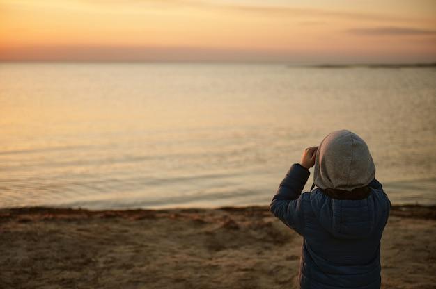Любопытный маленький мальчик смотрит в бинокль на красивую прибрежную природу на закате. изучение природы