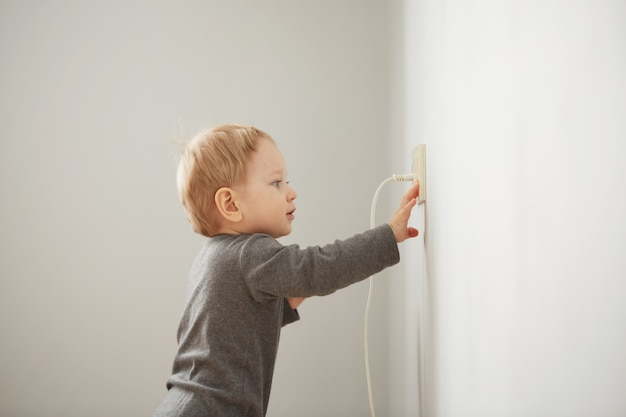 Curious little boy playing with electric plug