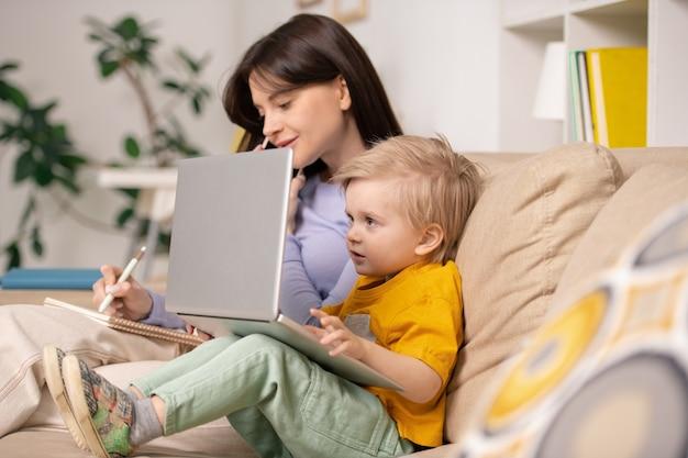 Любопытный маленький мальчик сидит на диване и смотрит мультфильм на ноутбуке, пока мать отвечает на телефонный звонок