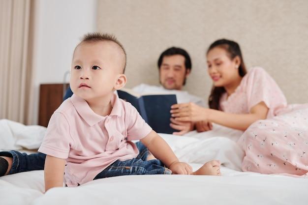 Любопытный маленький мальчик смотрит мультфильм по телевизору на стене, когда его родители читают книгу в фоновом режиме