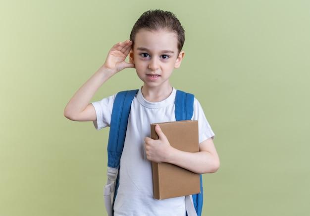 好奇心旺盛な少年がバックパックを身に着けて本を持ってカメラを見て、コピースペースのあるオリーブグリーンの壁に隔離されたジェスチャーを聞くことができません