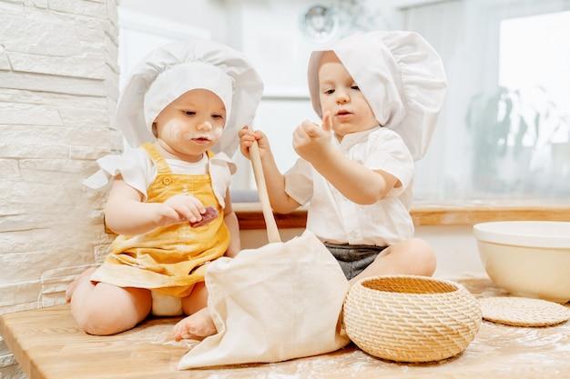 帽子をかぶった好奇心旺盛な小さな魅力的な料理人の子供たちは、生地を準備し、焼くための材料を研究します