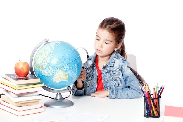 세계에서 돋보기를 통해 보고 있는 호기심 어린 소녀