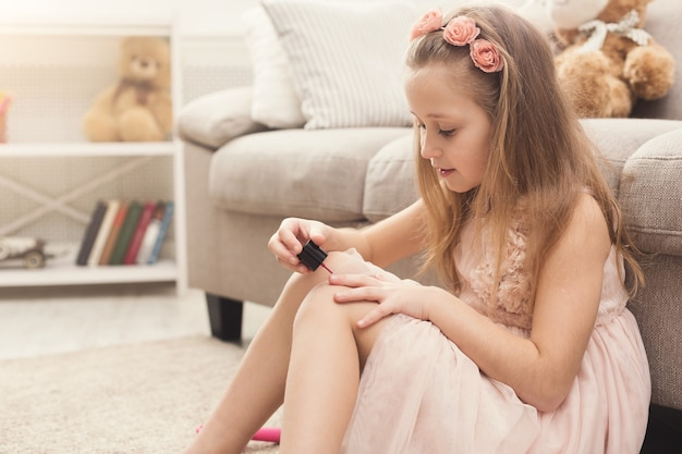 Curious little girl polishing her nails, sitting on floor at home. princess in pink dress making herself beautiful, copy space