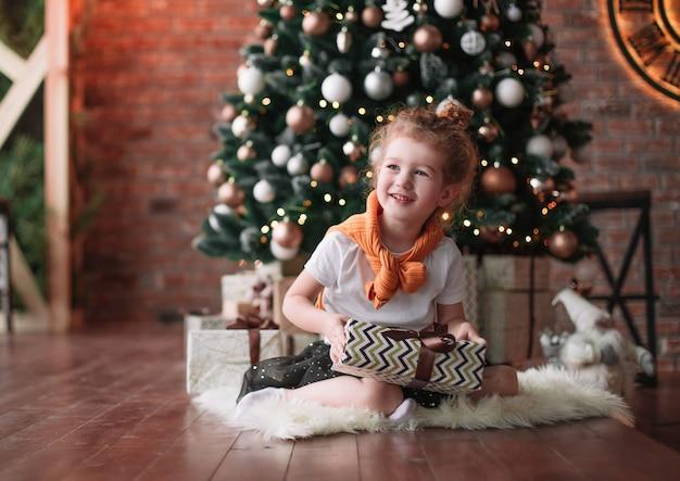 크리스마스 트리 근처에 앉아 호기심 어린 소녀.