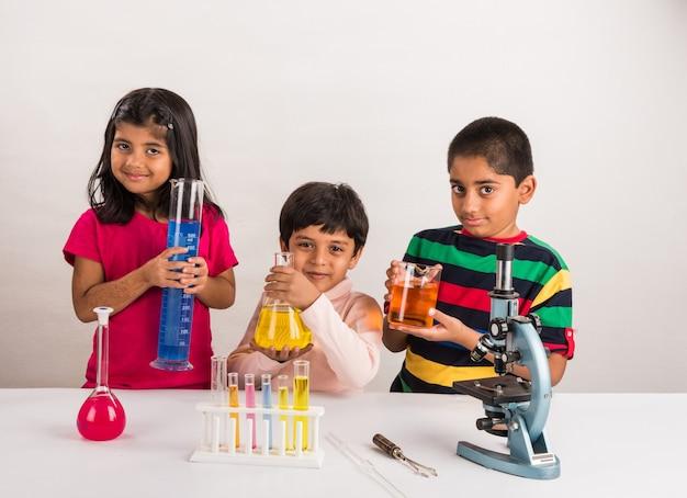 호기심 많은 인도 학교 어린이 또는 과학을 공부하는 과학자, 실험실에서 화학 물질 또는 현미경 실험, 선택적 초점