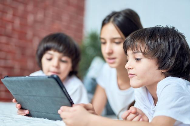 태블릿 pc 화면을 보고 있는 호기심 많은 라틴 소년. 형제는 형제들과 시간을 보내고, 게임을 하고, 집에서 침대에 누워 있습니다. 행복한 아이들, 기술 개념. 선택적 초점