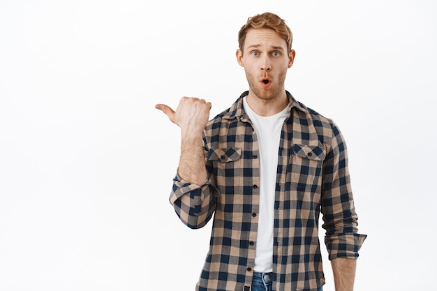 Curious man asking question about banner, pointing finger aside at logo, demonstrate advertisement and say wow, being impressed by promotion text, standing over white wall