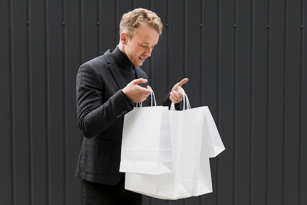 Curious man in black looking in shopping bags