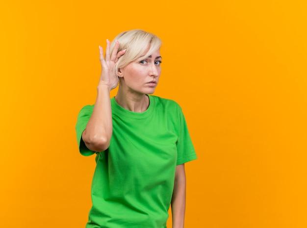 黄色い壁に孤立したジェスチャーが聞こえない前を見て好奇心旺盛な中年金髪女性