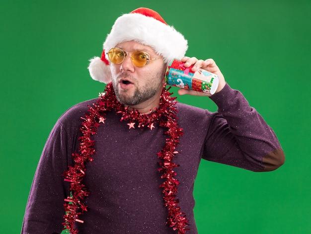 플라스틱 크리스마스 컵을 들고 안경 목에 산타 모자와 반짝이 갈 랜드를 입고 호기심 중년 남자