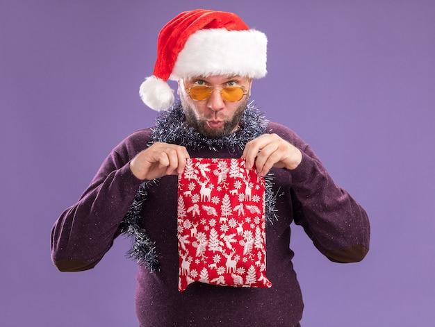 Curioso uomo di mezza età che indossa il cappello della santa e la ghirlanda di orpelli intorno al collo con gli occhiali che tengono il sacco del regalo di natale aprendolo isolato sul muro viola