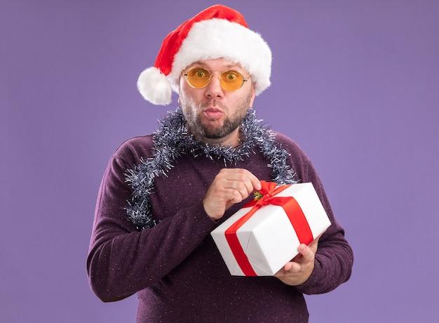 Curioso uomo di mezza età che indossa il cappello della santa e la ghirlanda di orpelli intorno al collo con gli occhiali che tengono il pacchetto regalo afferrando il nastro guardando la telecamera isolata su sfondo viola