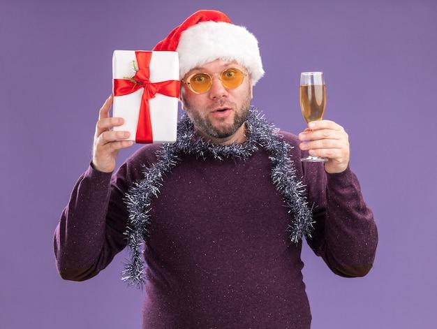 Curioso uomo di mezza età che indossa il cappello della santa e la ghirlanda di orpelli intorno al collo con gli occhiali che tengono il pacchetto regalo vicino alla testa e un bicchiere di champagne isolato sul muro viola