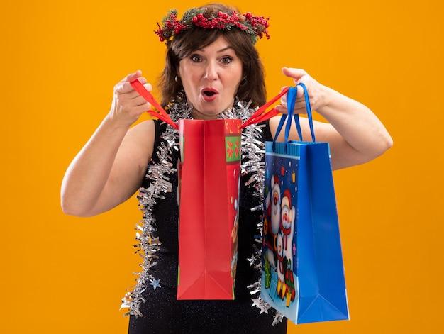 오렌지 배경에 고립 된 카메라를보고 하나를 열고 크리스마스 선물 가방을 들고 목 주위에 크리스마스 머리 화 환과 반짝이 갈 랜드를 입고 호기심 중년 여성