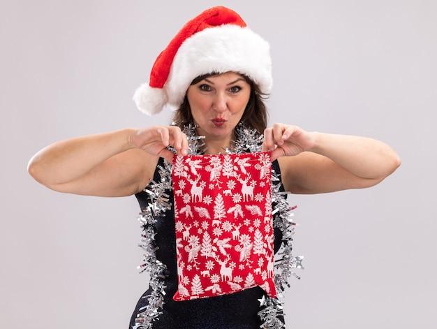 크리스마스 선물 자루를 들고 목에 산타 모자와 반짝이 갈 랜드를 입고 호기심이 중년 여성이 흰색 배경에 고립 된 카메라를보고 열어