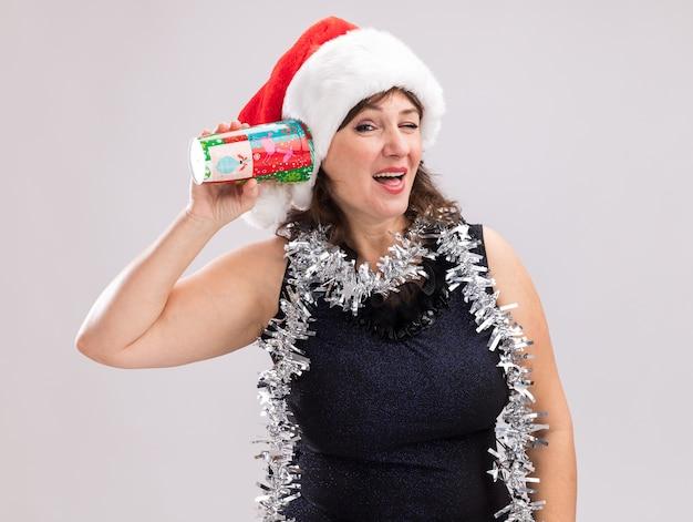 흰색 배경에 고립 윙크 카메라를보고 비밀을 듣고 귀 옆에 플라스틱 크리스마스 컵을 들고 목에 산타 모자와 반짝이 갈 랜드를 입고 호기심 중년 여성