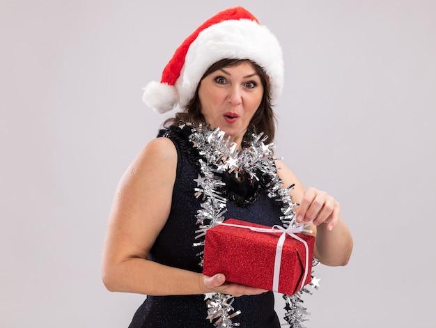 Curiosa donna di mezza età che indossa cappello da babbo natale e ghirlanda di orpelli intorno al collo che tiene il pacchetto regalo di natale che afferra il nastro guardando la telecamera isolata su sfondo bianco