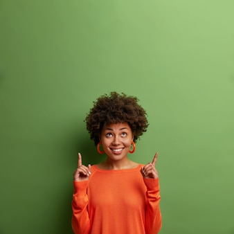 好奇心旺盛な喜んでいる暗い肌の女性モデルは上向きに見え、空のスペースを指して、プロモーションを示し、緑の壁に隔離された2階に行くことを提案します。このオファーを確認してください