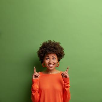 Il modello femminile dalla pelle scura e compiaciuto curioso guarda verso l'alto e indica lo spazio vuoto, dimostra il promo, suggerisce di andare al piano di sopra, isolato sul muro verde. controlla questa offerta