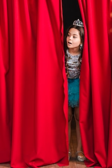 Curious pretty girl peeking from red curtain on stage