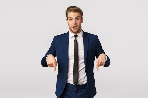 Curious and questioned young newbie consulting manager, asking advice, pointing down to ask question about interesting product, good-looking handsome businessman have something offer