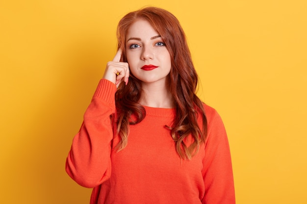 Curious red haired european woman concentrated above, tries to decide something, stands in thoughtful pose, keeps finger near lips, wears orange sweater