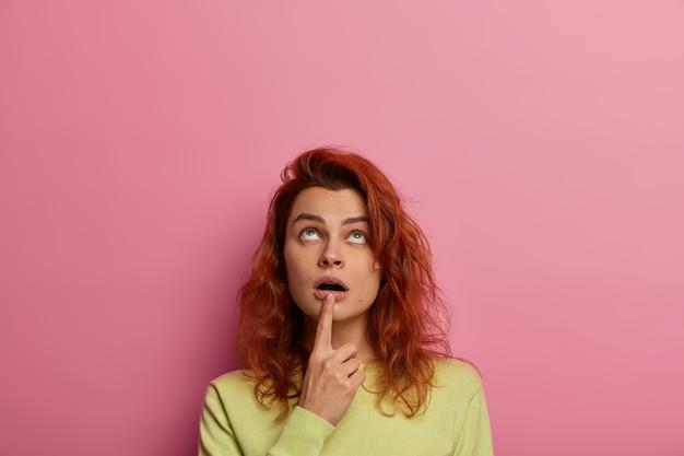 Любопытная рыжеволосая женщина удивленно смотрит наверх, держит указательный палец возле открытого рта, замечает странную вещь