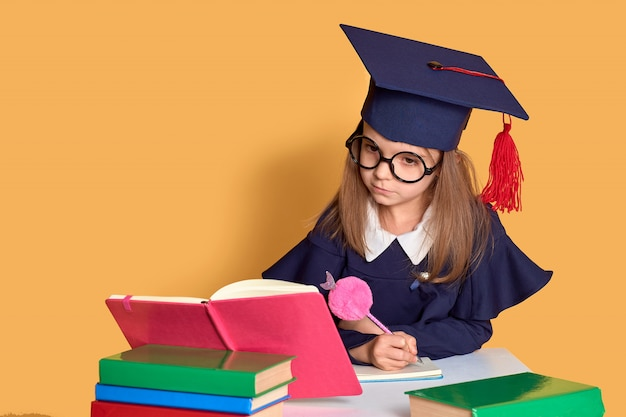 Curious schoolgirl in graduation outfit studying with textbooks