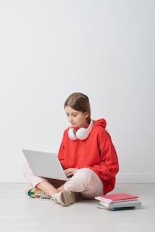 Любопытная школьница с беспроводными наушниками на шее выполняет онлайн-задание на ноутбуке