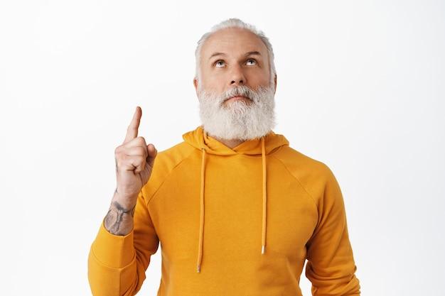 L'uomo anziano curioso con i tatuaggi guarda e punta verso l'alto, legge il testo promozionale sopra la testa, in piedi in felpa con cappuccio contro il muro bianco