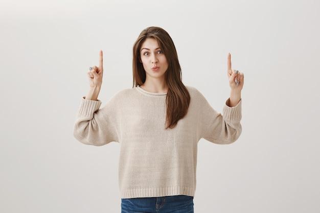 Любопытная глупая девушка показывает объявление вверх, показывает пальцами вверх и заинтригованно надувается