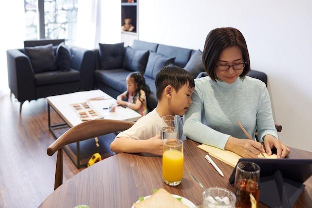 Любопытный маленький мальчик пьет стакан воды и смотрит на свою мать, которая пишет список покупок или пластику на день