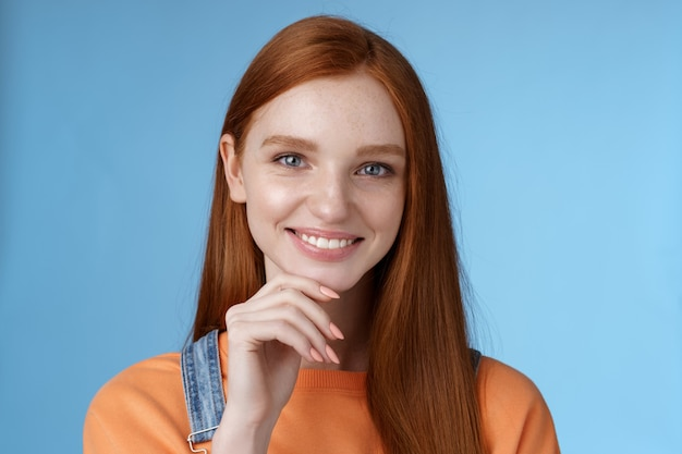 Curious smart creative young female redhead blue eyes have perfect idea how spend summer vacation smiling joyful look intrigued thoughtful touch chin pondering choice standing blue background
