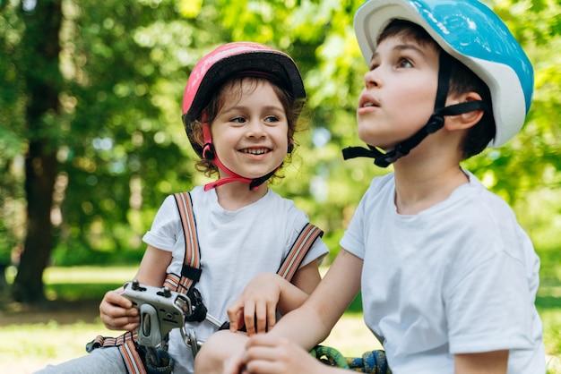 好奇心旺盛で笑顔の男の子と女の子がかわいい屋外でコミュニケーションします。かわいい子供たちは話すのが楽しい