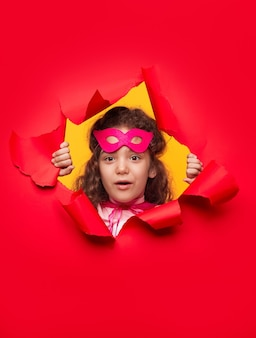 Curious superhero girl looking through hole in paper