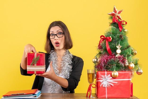 Curiosa donna d'affari sorpresa in vestito con gli occhiali che tiene il suo regalo e seduto a un tavolo con un albero di natale su di esso in ufficio