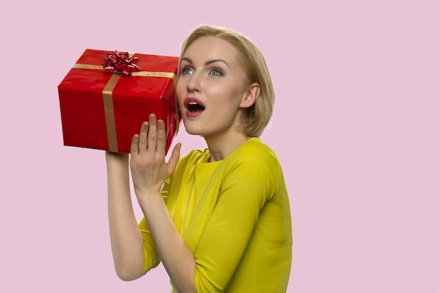 Curious surprised european lady with a gift box
