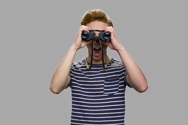 双眼鏡で見ている好奇心旺盛な10代の少年。灰色の背景に双眼鏡を使用してストライプのtシャツでショックを受けた10代の少年。