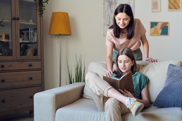好奇心旺盛な10代の少女がソファでリラックスしたポーズで座って本を読んでいる間、母親は彼女の趣味をサポートしています
