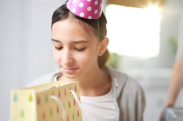 호기심 많은 10대 히스패닉 소녀가 집에서 생일을 축하하면서 선물 가방 안을 들여다보고 확인합니다. 축하, 어린 시절 개념