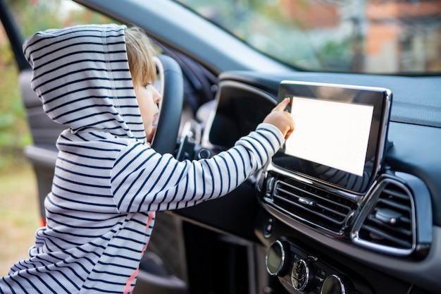 Curious toddler girl holding touching and turning a car mnultiedia touch screen player button