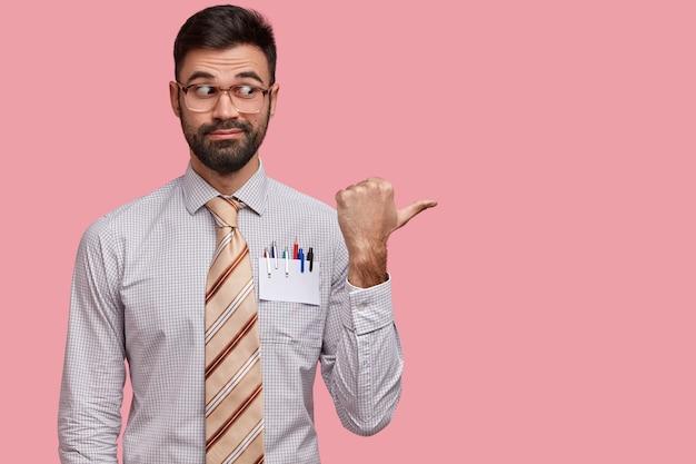 L'uomo curioso con la barba lunga ha setole scure, punta da parte con il pollice, pubblicizza qualcosa di attraente