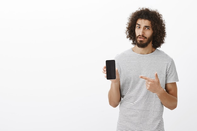 Curious unsure handsome bearded man with curly hair, showing black smarpthone and pointing at gadget
