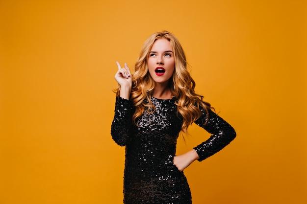 Любопытная хорошо одетая девушка, стоящая на желтой стене. задумчивая блондинка молодая женщина в черном платье думает о чем-то.