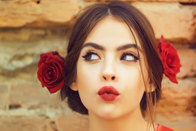 Curious woman or cute girl, young fashion model with red lips, makeup and fresh roses, flowers in brunette hair, fashionable hairstyle posing outdoors on old brick wall. beauty and hairdressing salon