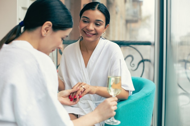Curious woman looking at the engagement ring of her smiling friend and drinking champagne with her